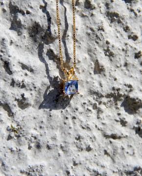 Kette mit Anhänger Maria gelbgold tansanite blau frontal vor Wand