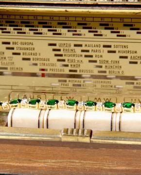 Armband Sissi gelbgold smaragd grün weiß liegend auf Radio